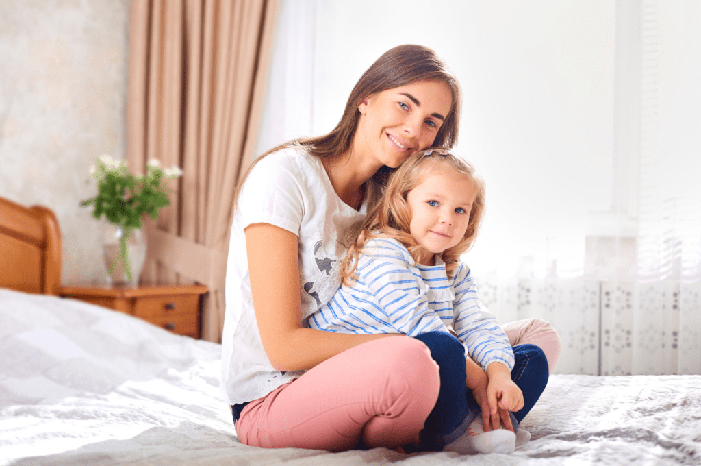 single mom guilt - mom and daughter sit together on bed